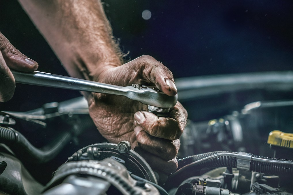 mechanic turning wrench on a car